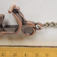 Robogó kulcstartó bronz színben